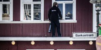 Verkamaður þrífur glugga í bankastræti