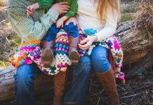 Foreldrar sitja á bekk og halda á barni