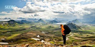 Útivistargarpur með stóran bakpoka stendur og horfir yfir fallegt landsvæði