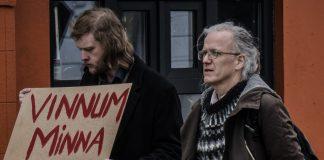"""tveir menn standa saman og annar þeirra heldur á skilti með textanum """""""""""